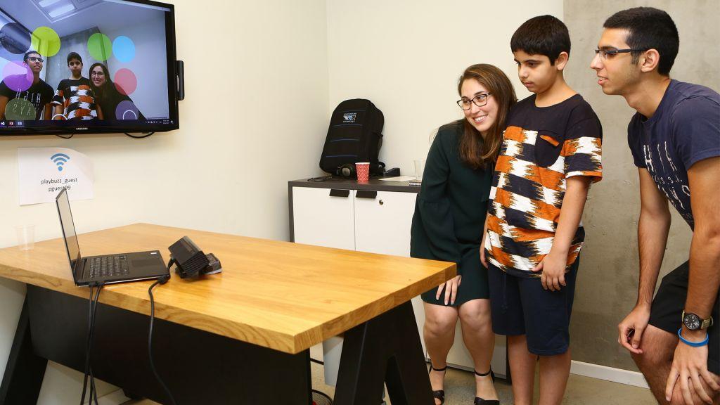 Les participants essaient une technologie développée à l'hackathon. (Crédit : Dror Sitahkol)