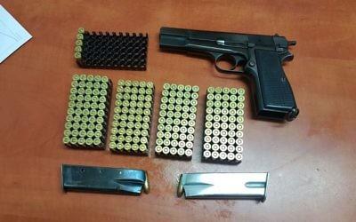 Le pistolet, les munitions et les magasins saisis dans une opération menée dans une habitation familiale de la ville de Hébron le 2 août 2017 (Crédit : Police israélienne)