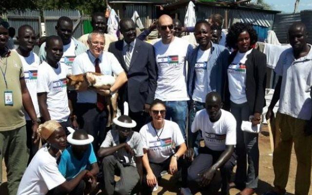 L'ambassadeur israélien au Soudan du Sud, Hanan Doger, distribue de la nourriture aux villageois aux côtés de membres du gouvernement et de représentants de groupes humanitaires israéliens, en août 2017. (Crédit : ambassade d'Israël au Soudan du Sud)