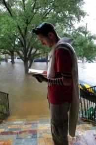 Rafi Engelhart, émissaire du mouvement Bnai Akiva de Houston, prie devant l'habitation inondée ans laquelle sa famille s'est réfugiée face à la tempête tropicale Harvey, le 27 août. (Autorisation)