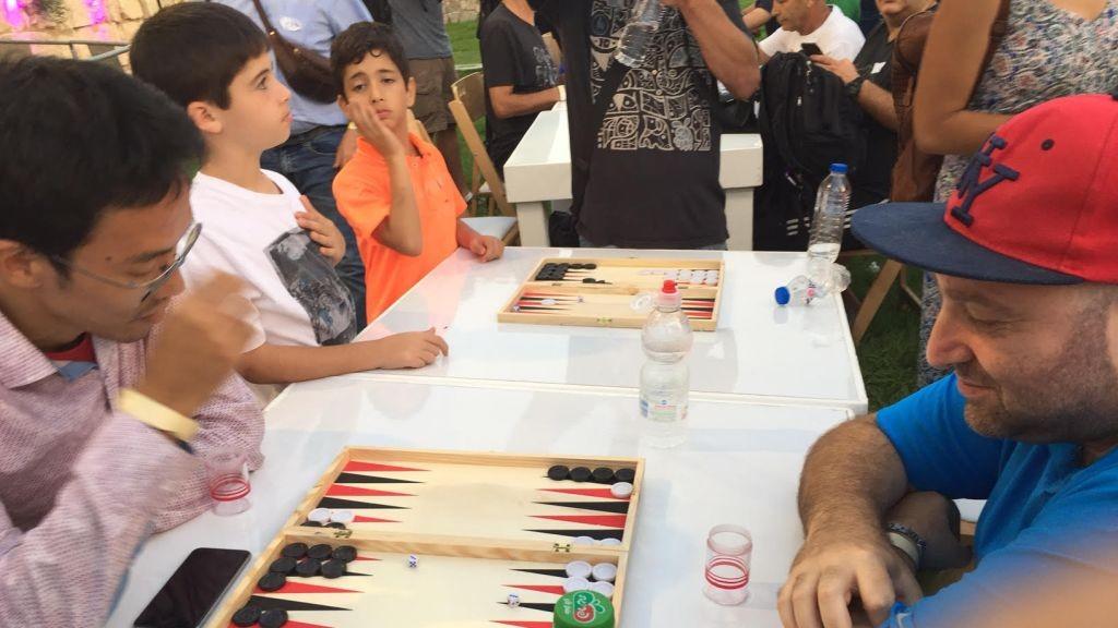 Deux joueurs internationaux, Falafel (à droite) et l'ancien champion du monde Mochy Mochizuki, dans les jeux de qualification du Championnat de Backgammon, derrière la Vieille Ville de Jérusalem, le 24 août 2014. (Crédit : Times of Israel)