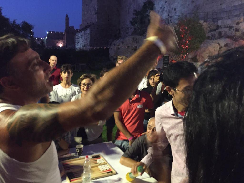 Ayal Amari célèbre sa victoire face à l'ancien champion du monde Mochy Mochizuki dans un match qualificatif du Championnat de Backgammon, derrière la Vieille Ville de Jérusalem, le 24 août 2014. (Crédit : Times of Israel)