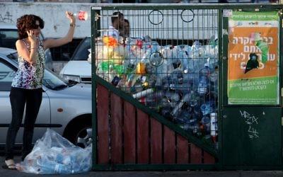 Une femme jette une bouteille dans un conteneur de recyclage à Jérusalem. (Nati Shohat/Flash90)