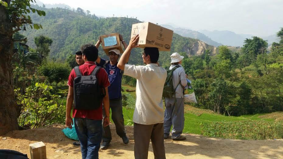Les travailleurs humanitaires népalais transportent des fournitures qu'ils ont reçus d'Israël (crédit : Tevel bTzedek)
