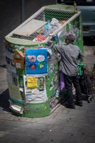 Un homme âgé recherche une poubelle de recyclage pour prendre des bouteilles en plastique qu'il pourra faire rembourser à Jérusalem, le 23 juillet 2017 (Crédit : Nati Shohat/FLASH90)