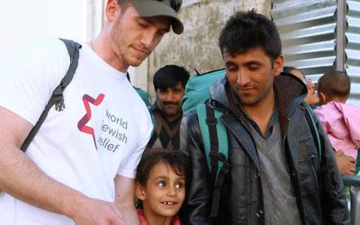 Un volontaire de l'organisation World Jewish Relief travaille avec des réfugiés en Grèce (Crédit : Minos Alchanati / via JTA)