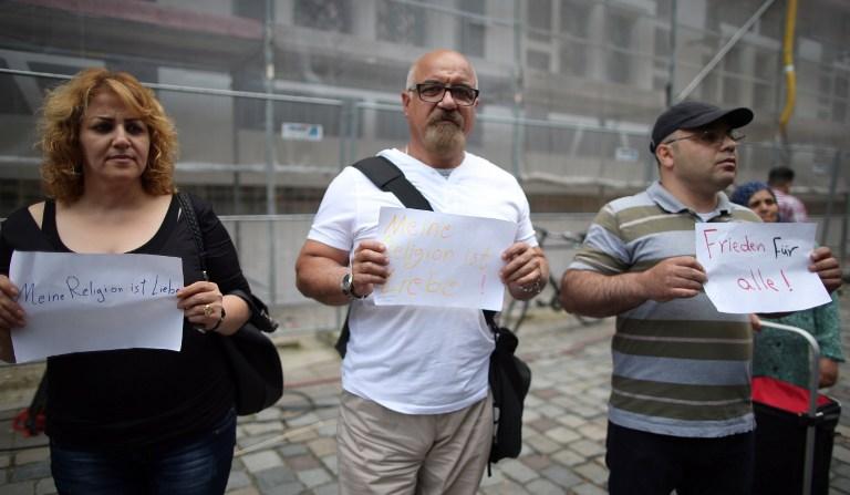 Des réfugiés irakiens et syriens tiennent des panneaux disant 'ma religion est l'amour' et 'paix à tous' aux abords du site d'un attentat-suicide à la bombe à Ansbach, dans le sud de l'Allemagne, le 26 juillet 2016 vingt quatre heures après qu'un terroriste âgé de 27 ans a blessé 15 personnes (Crédit : AFP PHOTO/dpa/Daniel Karmann)