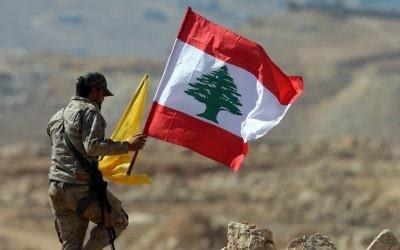 Un membre du groupe terroriste du Hezbollah tient des drapeaux libanais et du Hezbollah durant une visite organisée pour la presse à côté de la ville frontalière d'Arsal, le 25 juillet 2017 (Crédit : Stringer/AFP)