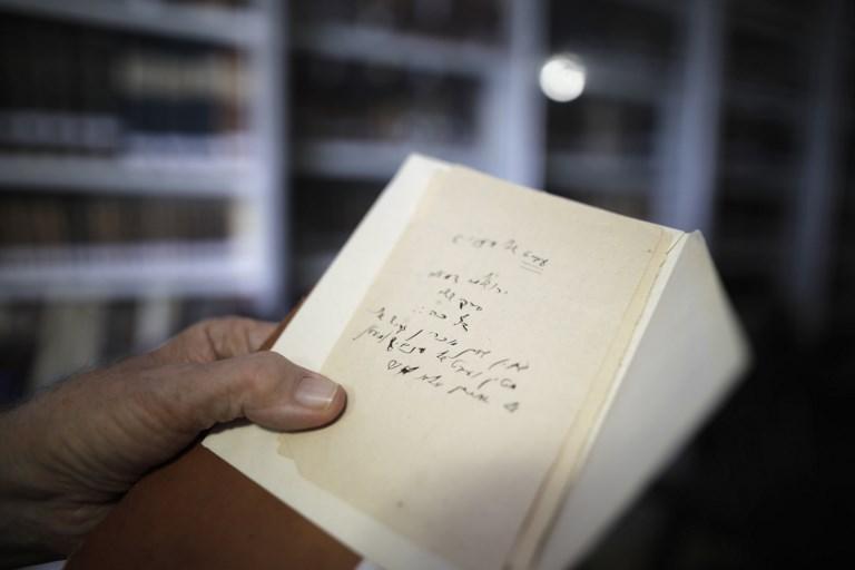 Gabriel Birnbaum, chercheur au Historical Dictionary Project de l'Académie israélienne de la langue hébraïque, tenant un papier avec les notes manuscrites d'Eliezer Ben-Yehuda sur les termes hébraïques. Ben-Yehuda est considéré comme le père de l'hébreu moderne, à Jérusalem, le 23 août 2017 (Crédit : AFP / MENAHEM KAHANA)