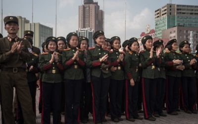Les soldats de l'Armée populaire de Corée du nord applaudissent alors qu'ils regardent un écran montrant le lancement d'un test de missile sur une place publique, aux abords d'une gare de Pyongyang, le 30 août 2017. (Crédit : AFP/Kim Won-Jin)