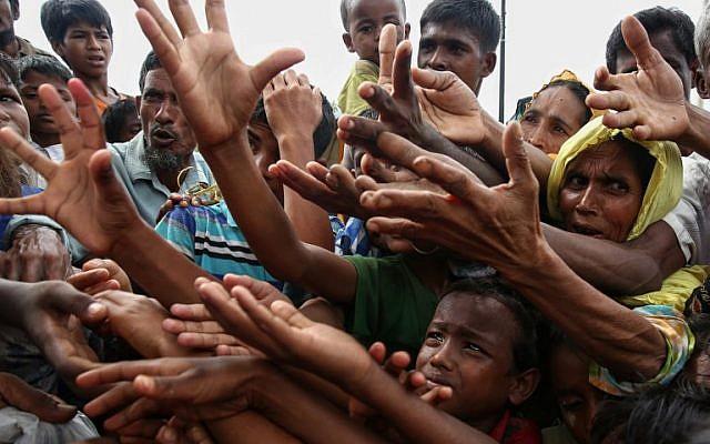 Des réfugiés Rohingyas demandent une aide alimentaire dans le camp de réfugiés de Kutupalong à Ukhiy, à proximité de la frontière entre le Myanmar et le Bangladesh, le 30 août 2017 (Crédit : Stringer/AFP)
