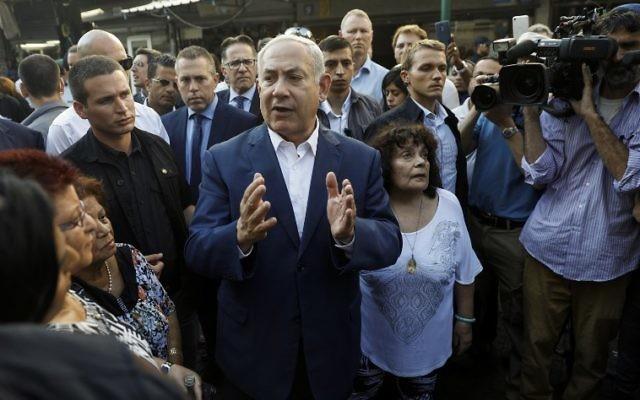 Le Premier ministre israélien Benjamin Netanyahu parle avec les résidents du sud de Tel Aviv lors d'une visite dans la ville, le 31 août 2017 (Crédit : AFP PHOTO / Menahem KAHANA)