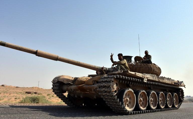Les forces gouvernementales syriennes à bord d'un tank dans le village de Kobajjep, au sud-ouest de la province de Deir es-Zor, le 6 septembre 2017. (Crédit : George Ourfalian/AFP)