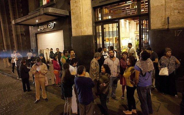 Les gens se rassemblent dans une rue dans le centre-ville de Mexico lors d'un tremblement de terre le 7 septembre 2017 (Crédit : AFP PHOTO / PEDRO PARDO)
