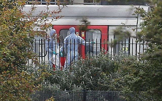 Des techniciens médico-légaux travaillent à côté du métro arrêté à la station Parsons Green située à l'ouest de Londres, le 15 septembre 2017, suite à l'explosion d'un engin artisanal (Crédit : (AFP/Daniel Leal-Olivas)