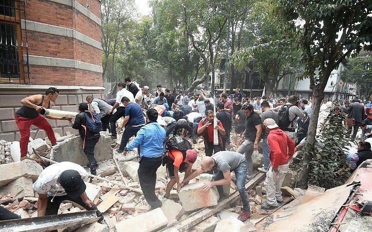 Des habitants tentent de déblayer des ruines et de secourir des personnes coincées sous les décombres après un séisme qui a touché Mexico et fait au moins 224 morts dans le centre du Mexique, le 19 septembre 2017. (Crédit : Alfredo Estrella/AFP)