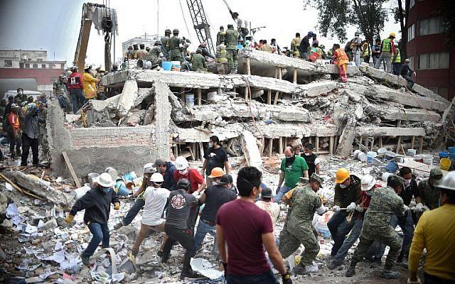 Les secouristes, les pompiers, les policiers, les soldats et les volontaires cherchent des survivants dans un bâtiment effondré au Mexique le 20 septembre 2017 (Crédit : AFP PHOTO / Yuri CORTEZ)