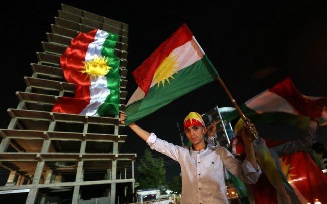 Kurdes irakiens avec leurs drapeaux pendant une manifestation appelant le peuple à voter au référendum d'indépendance, à Erbil, la capitale de la région autonome du Kurdistan irakien, le 22 septembre 2017. (Crédit : Safin Hamed/AFP)