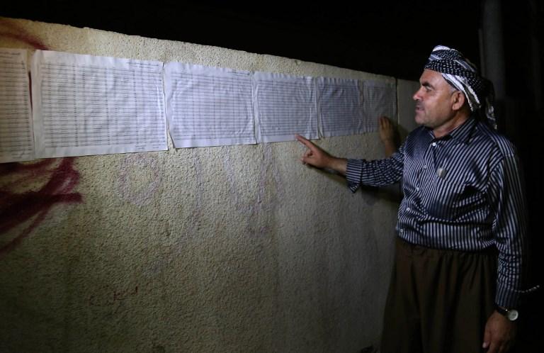 Un Kurde irakien devant les listes électorales affichées devant un bureau de vote d'Erbil, à la veille du référendum sur l'indépendance du Kurdistan irakien, le 24 septembre 2017. (Crédit : Safin Hamed/AFP)
