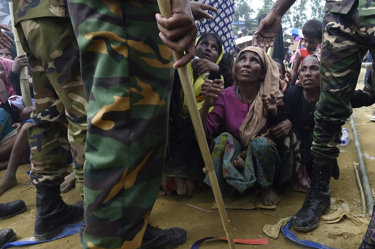 Des soldats de l'armée du Bangladesh montent la garde alors que des réfugiés rohingyas musulmans, qui ont traversé la frontière depuis le Myanmar, attendent de recevoir une aide durant une distribution à proximité du camp de réfugiés de Balukhali, au Bangladesh, le 25 septembre 2017. (Crédit : Dominique Faget/AFP Photo)