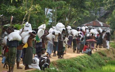 Des réfugiés musulmans Rohingya transportent de la nourriture distribuée par l'armée du Bangladesh au camp de réfugiés Balukhali près de Gumdhum, le 26 septembre 2017. (Crédit : AFP PHOTO/Dominique FAGET)