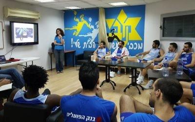 Lehi Segal, debout, de DayTwo, parle nutrition avec les membres de l'équipe nationale de basketball d'Israël. (Crédit : DayTwo)