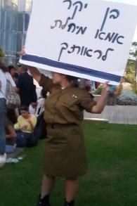 """Une soldate avec un panneau """"Cher fils, maman attend de voir"""" pendant une manifestation de centaines d'Israéliens pour la reconnaissance gouvernementale de l'affaire des enfants yéménites, à Tel Aviv, le 25 septembre 2017. (Crédit : Times of Israël)"""