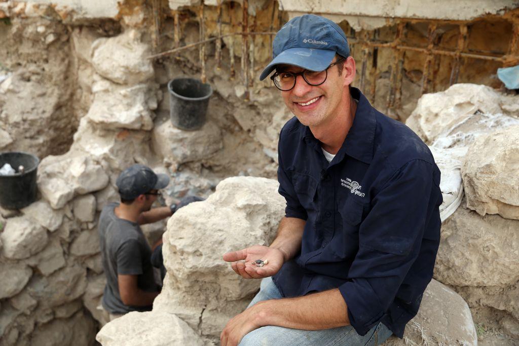 Le docteur Joe Uziel tient des sceaux de l'époque du Premier Temple, dans la Ville de David, à Jérusalem, en août 2017. (Crédit : Eliyahu Yanai / Ville de David)
