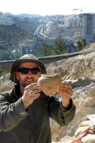 Alex Wigman, archéologue de l'Autorité israélienne des antiquités, montre une jarre sortie d'une tombe cananéenne à Jérusalem (Crédit : Shua Kisilevitz, Autorité israélienne des antiquités)