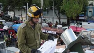 Un soldat israélien examine les dommages causés à un immeuble par un violent séisme, à Mexico, le 24 septembre 2017. (Crédit : armée israélienne)