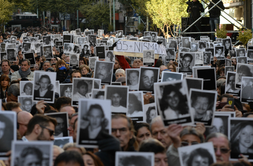Des participants brandissent des photos de certaines des 85 victimes lors d'une cérémonie de commémoration de l'attentat à la bombe commis au centre communautaire juif de l'AMIA de Buenos Aires, le 18 juillet 2016 (Crédit : Leonardo Kremenchuzky, autorisation AMIA/Via JTA)