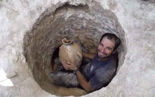 David Tanami, archéologue de l'Autorité israélienne des Antiquités, s'active autour de l'ouverture étroite d'une tombe pour en sortir une jarre sur un site funéraire cananéen aux abords du zoo biblique de Jérusalem (Crédit : Shua Kisilevitz, Autorité israélienne des antiquités)