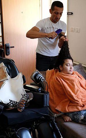 Hamdi Aman coiffe les cheveux de sa fille Maria, tétraplégique, dans leur maison du quartier de Beit Safafa à Jérusalem, le 23 août 2017 (Crédit : Judah Ari Gross/Times of Israel)