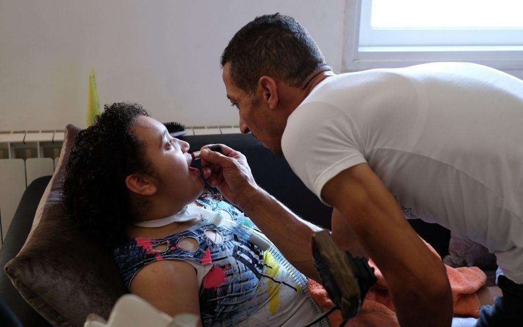 Hamdi Aman met du rouge à lèvres à sa fille Maria, tétraplégique, dans leur appartement du quartier Beit Safafa de Jérusalem le 23 août 2017 (Crédit : Judah Ari Gross/Times of Israel)