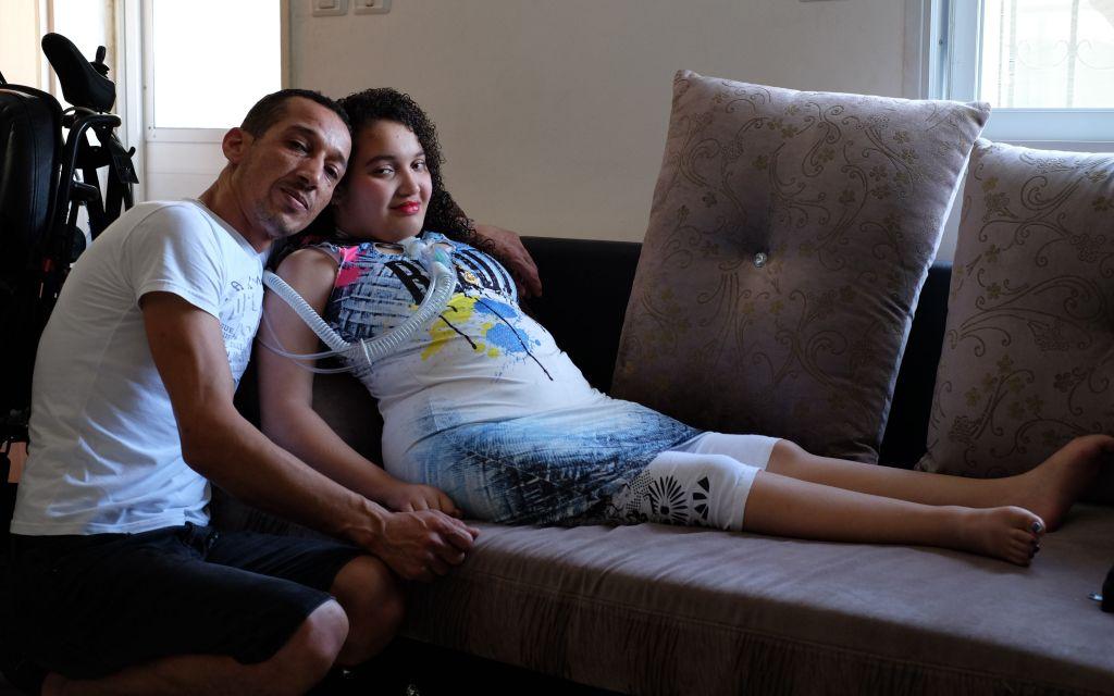 Maria Aman, tétraplégique suite à une frappe aérienne israélienne à Gaza, en 2006,  et son père dans le salon dans leur appartement du quartier Beit Safafa de Jérusalem le 23 août 2017 (Crédit : Judah Ari Gross/Times of Israel)