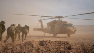 Des soldats courant vers un hélicoptère pendant un exercice de l'armée israélienne simulant une guerre contre le Hezbollah, dans le nord d'Israël, en septembre 2017. (Crédit : armée israélienne)