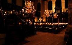 L'intérieur de la synagogue portugaise d'Amsterdam illuminée par les bougies (Crédit :  CC BY-SA Massimo Catarinella, Wikimedia)