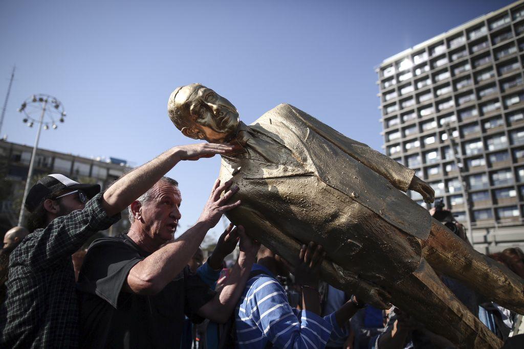 Une statue dorée du Premier ministre Netanyahu est renversée sur la place Rabin de Tel Aviv, le 6 décembre 2016 (Crédit : Miriam Alster/Flash90)