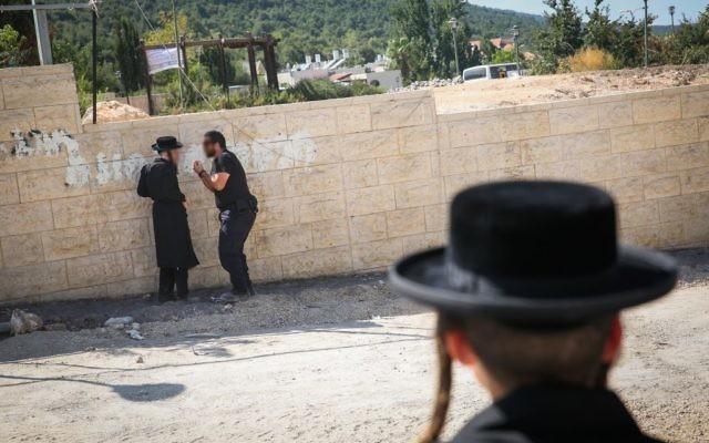 Illustration : altercation entre un policier et un manifestant ultra-orthodoxe sur un chantier à Méron, dans le nord d'Israel, le 16 août 2017. (Crédit : David Cohen/Flash90)