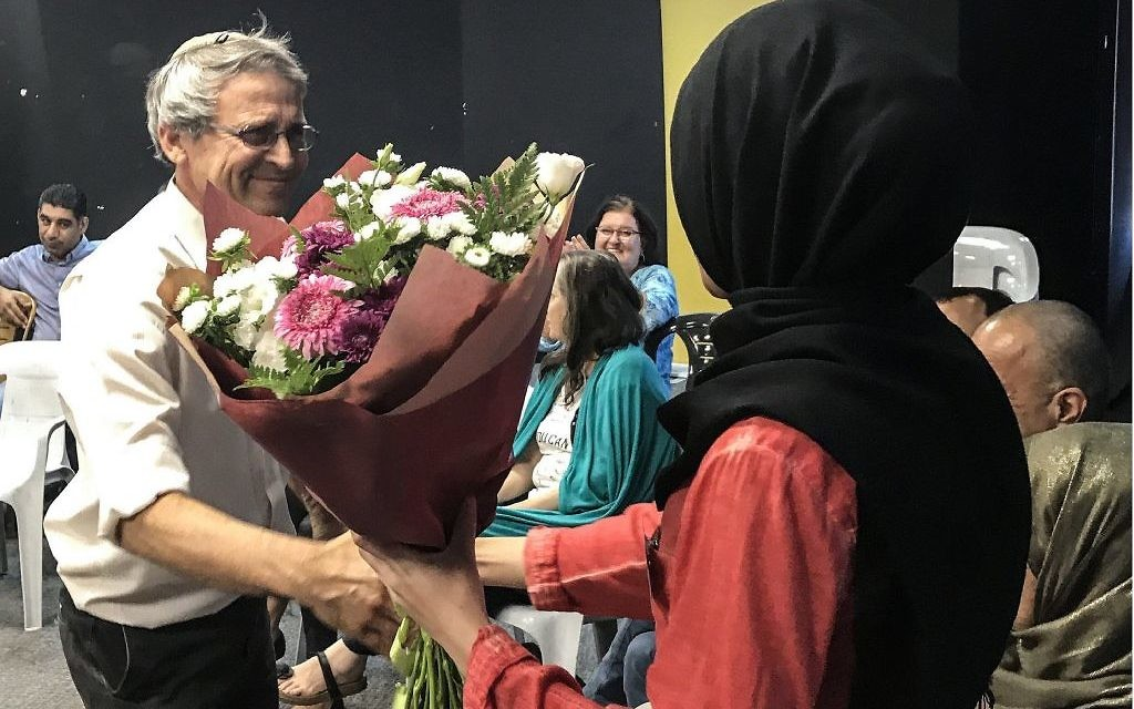Le fondateur de Tag Meir, Gadi Gvaryahu, donne un bouquet de fleurs à Mervat Igbaria, étudiante qui a été confondue avec un terroriste lors d'un trajet d'autobus vers Beer Sheva (Crédit : Gabriel Carrol / Times of Israel)