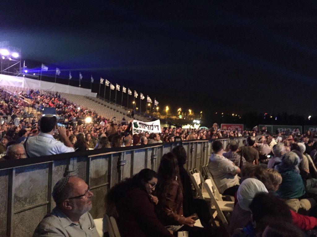 Des habitants de l'avant-poste illégal Netiv Haavot appellent le Premier ministre Benjamin Netanyahu à éviter la destruction de leurs maisons pendant la cérémonie officielle de commémoration des 50 ans d'implantation israélienne en Cisjordanie et sur le plateau du Golan, le 27 septembre 2017. (Crédit : Chaim Goldman)