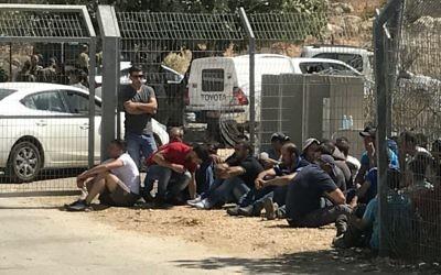 Des travailleurs palestiniens devant l'implantation de Har Adar, après l'attentat terroriste meurtrier du 26 septembre 2017. (Crédit : Jacob Magid/Times of Israël)