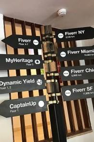 Un panneau indiquant les différents bureaux de Fiverr dans le hall d'un bâtiment historique à Tel Aviv (Crédit : Shoshanna Solomon / TimesofIsrael)