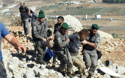 Les forces de sécurité arrêtent un résident d'implantation lors de la démolition d'un avant-poste illégal dans le nord de la Cisjordanie, le 28 septembre 2017 (Crédit : Autorisation Honenu)