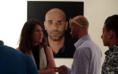 Luai Abed (à droite) se trouve devant une photo de lui-même lors d'une exposition d'œuvres du journaliste photo Tali Mayer, qui, elle-même, a été blessée par une balle recouverte de mousse en 2014 en couvrant une manifestation (Crédit : Ido Grumer)