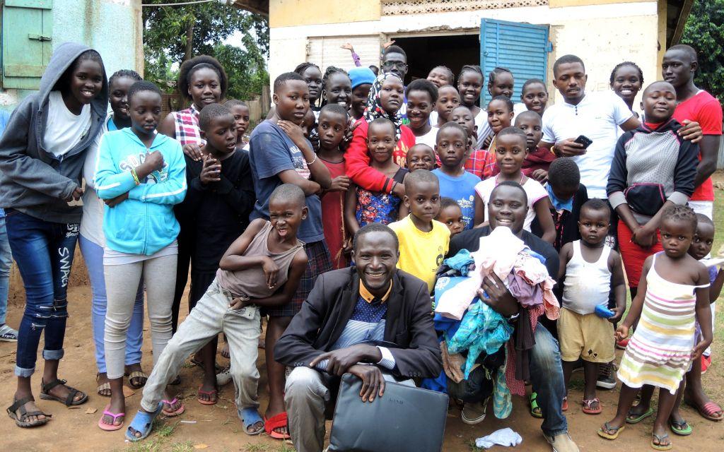 Jason Berry, le directeur pour l'Ouganda de Come True, au centre avec la mallette noire, avec les dons et autres fripes qui ont été distribués lors d'une journée de bénévolat de Come True à Kampala le 1er septembre 2017 (Crédit : Melanie Lidman/Times of Israel)