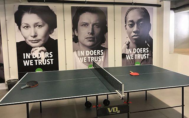 Le bureau de Fiverr à Tel Aviv : une table de ping-pong pour ses employés avec des œuvres d'art par des travailleurs indépendants avec le slogan de la startup : en les personnes de confiance nous faisons confiance, le 6 août 2017 (Crédit : Shoshanna Salomon / Times of Israel)