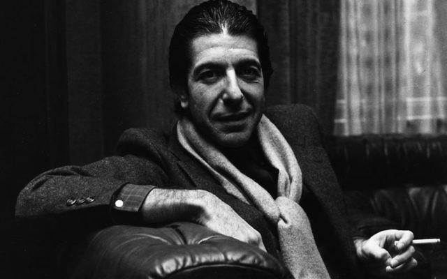 L'auteur-compositeur folk canadien  Leonard Cohen, solennel, partage toutefois une plaisanterie en fumant une cigarette (Crédit : Evening Standard/Getty Images/JTA)