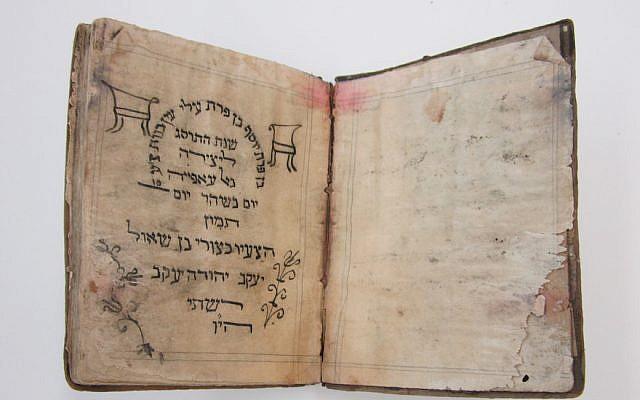 Une Haggadah de Pessah, de 1902, l'un des rares manuscrits en hébreu extirpés d'une cave inondée, de Mukhabarat, les quartiers généraux des services secrets de Saddam Hussein, décorée à la main par un jeune irakien. (Crédit : U.S. National Archives)