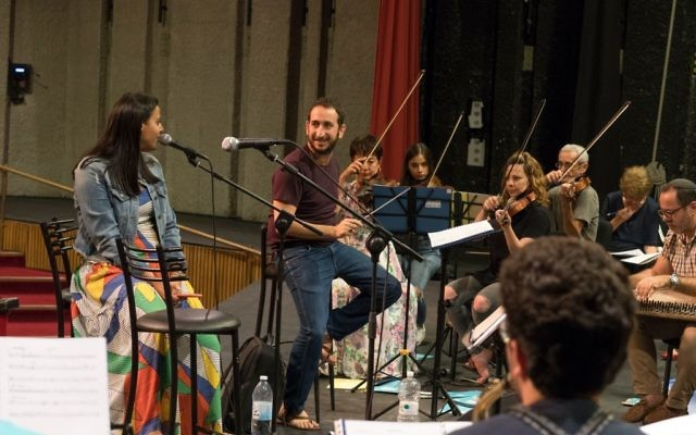 Le chef d'orchestre de l'Orchestre de Jérusalem Est-Ouest,   Tom Cohen, et la chanteuse  Nasreen Qadri, alors d'une répétition du concert 'Kulna' à Jérusalem (Crédit : Gil Rouvio/Mekudeshet)
